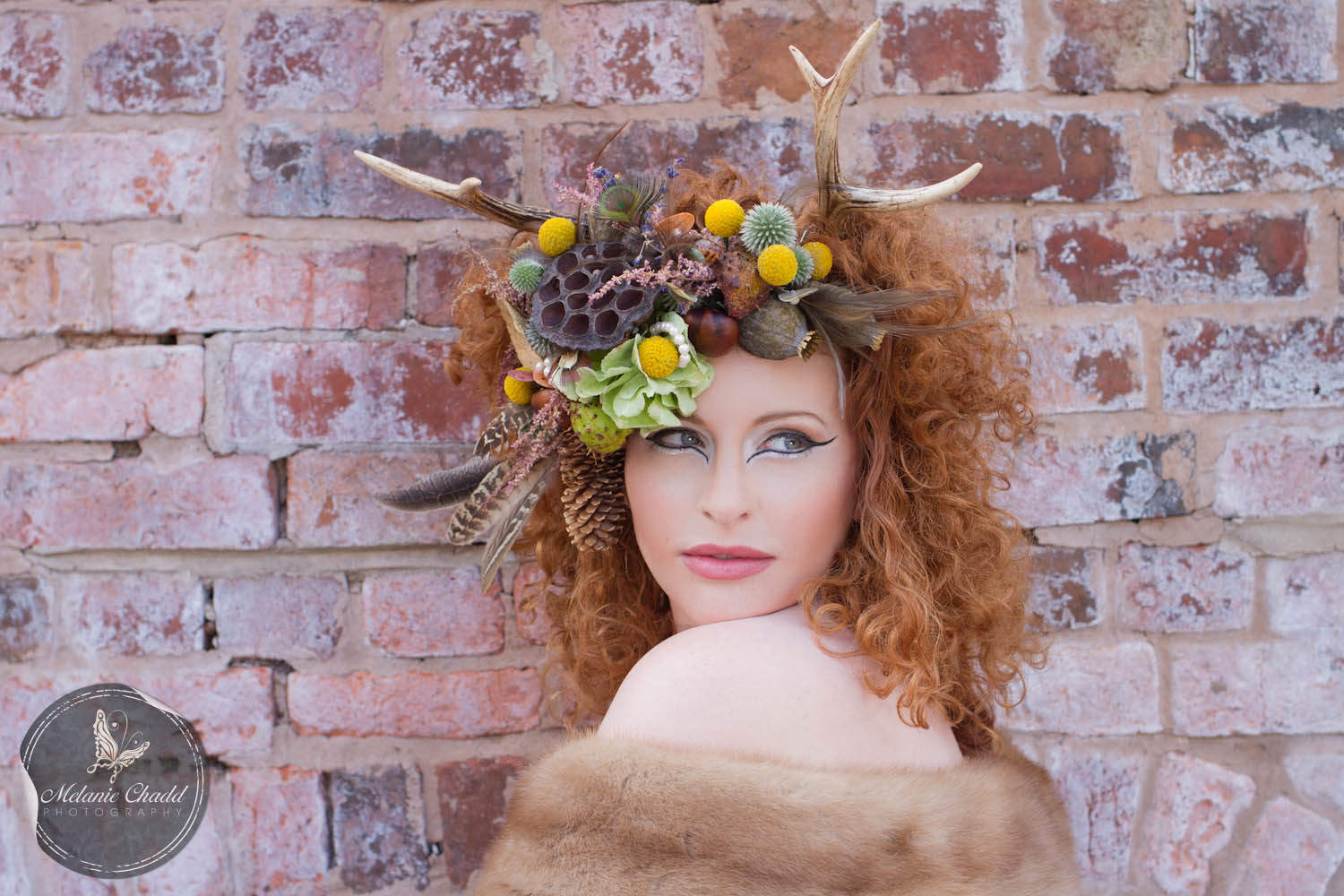 Model wearing antlers and a floral head dress