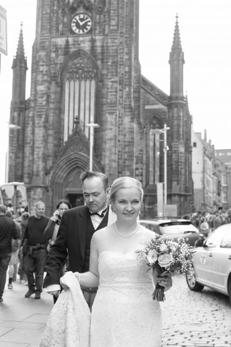 Black and white image of bride and groom on the Royal Mile, Edinburgh